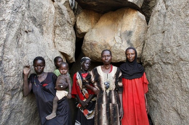 Women stand in front of a cave in Bram village in the Nuba Mountains, South Kordofan, April 28, 2012. Fleeing aerial bombardment by the Sudanese air force thousands of people have abandoned their homes and made make-shift shelters between the rocks and boulders. REUTERS/Goran Tomasevic (SUDAN - Tags: CIVIL UNREST SOCIETY TPX IMAGES OF THE DAY)